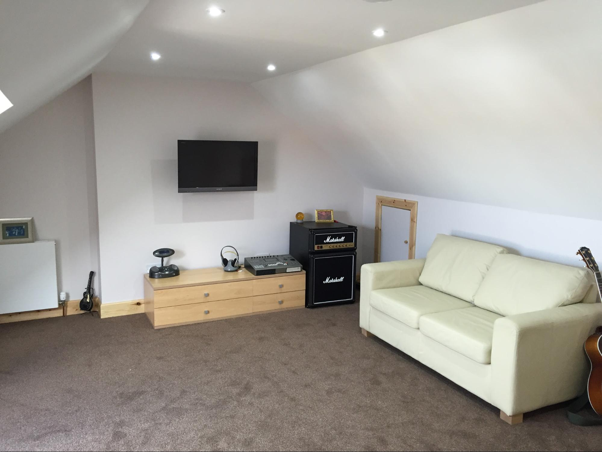 Loft conversion living area with couch and music equipment